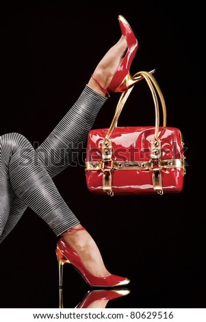 Hung on heel. Stylish red bag hanging on a chic high-heeled shoe. - stock photo