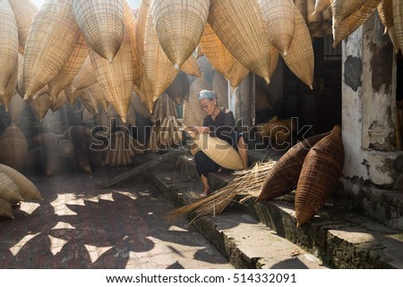 Hung Yen, Vietnam - July 9, 2016: Old house yard with many bamboo fish trap and female craftsman making traditional bamboo fish trap at her old house in Thu Sy trade village