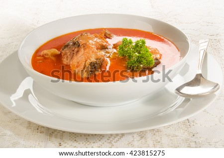 hungarian carp soup with sour cream in a white soup plate - stock photo