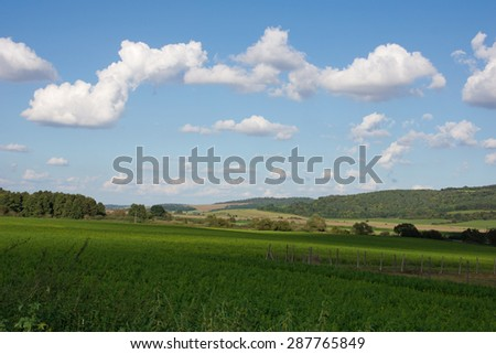 Hungarian landscape with hills and fields and a cloudy sky