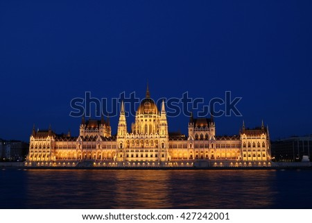 Hungarian Parliament along the Danube River in Budapest in the evening blue hours, illuminated by warm lighting - stock photo