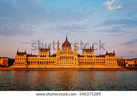 Hungarian Parliament on river at sunset, Budapest. Construction started  building in 1885 and completed in 1904.