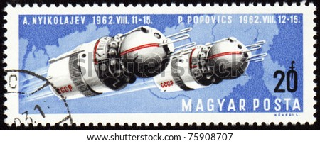 HUNGARY - CIRCA 1962: A stamp printed in Hungary shows soviet spaceships Vostok-3 and Vostok-4 with cosmonauts Nikolaev and Popovich in space, circa 1962 - stock photo