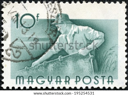 HUNGARY - CIRCA 1959: Green color stamp printed in Hungary with image of a river fisherman, circa 1959. - stock photo