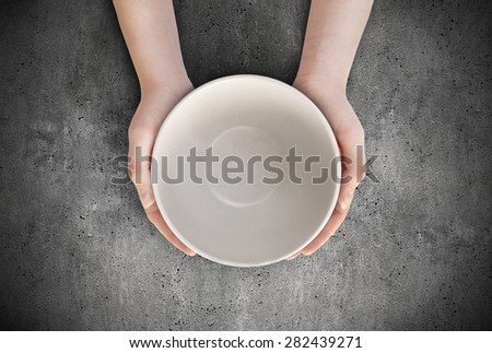 Hunger concept. Female holding empty plate waiting food. Empty plate in hand - stock photo