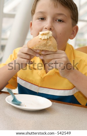 Hungry Appetite:  Child eating a banana muffin.  Focus on hands muffin. - stock photo