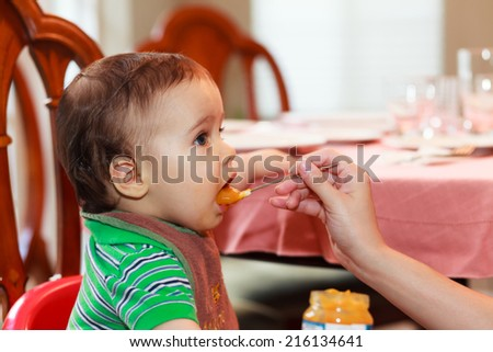 Hungry baby boy being fed a meal in a home setting.