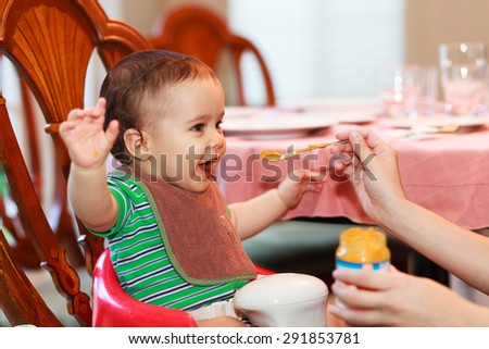 Hungry baby boy being fed a meal in a home setting. - stock photo
