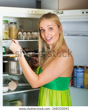 hungry blonde girl eating  soup from pan near fridge  - stock photo