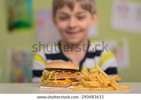 Hungry boy looking at big burger and chips - stock photo
