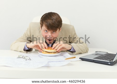 Hungry businessman eats for a tasty sandwich - stock photo