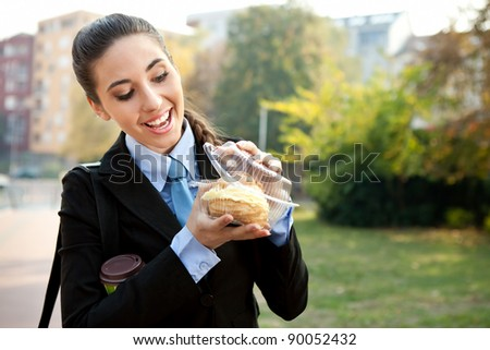 hungry businesswoman , smiling and looking in  donut, outdoor - stock photo