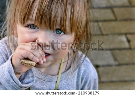 Hungry caucasian child with big clear eyes eating bread and impressively looking at the camera. Close-Up. - stock photo