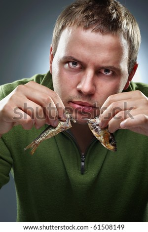 Hungry corpulent man with two halfs of fish in hands - stock photo