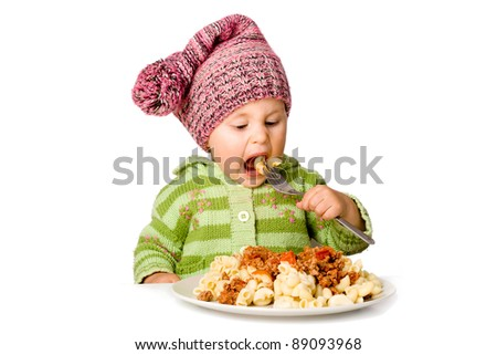 Hungry cute child eating pasta with plug; isolated over white