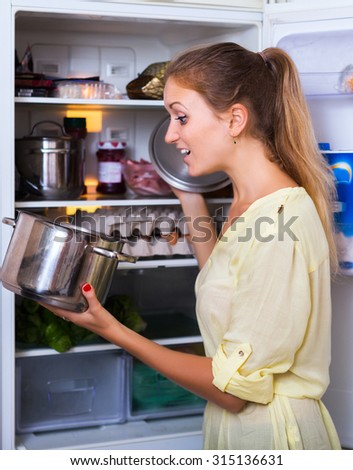 Hungry housewife posing with soup near opened refrigerator