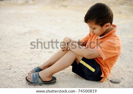 Hungry kid begging on the street with a crutches beside - stock photo