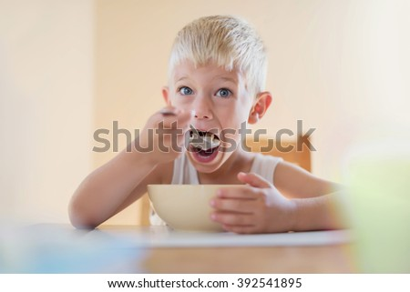 Hungry Kid Starving Eating Corn Flakes Cereals - stock photo