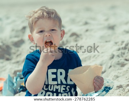 hungry kid with open mouth eating salty fat chips or junk food on the beach - stock photo