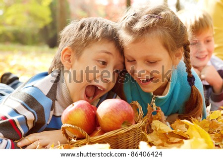 Hungry kids biting autumnal apples - stock photo