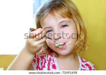 hungry little blond girl spoon eating ice cream pastry dirty mouth - stock photo