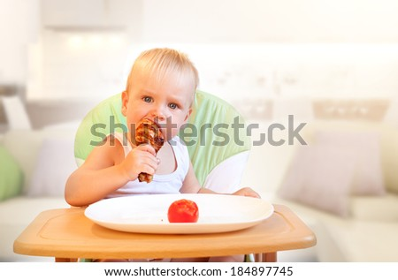 Hungry little  boy eat chicken. Yummy but harmful - stock photo