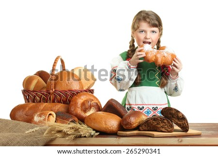 Hungry little girl biting a bun at the table - stock photo
