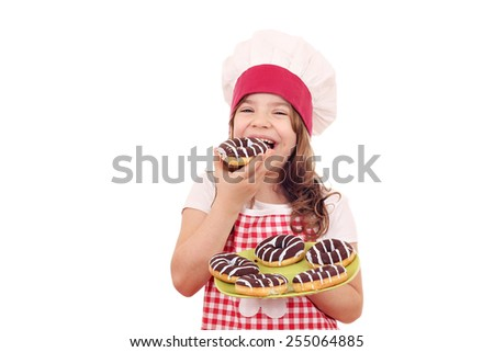 hungry little girl cook eating chocolate donuts - stock photo