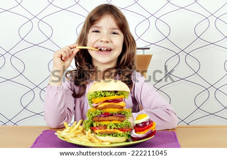 hungry little girl eat big hamburger and french fries - stock photo