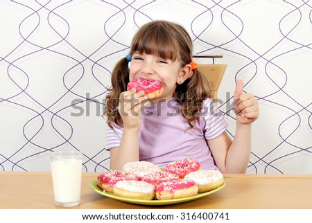 hungry little girl eat donuts  - stock photo