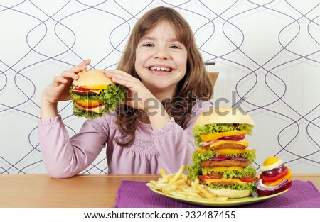 hungry little girl eat hamburger - stock photo