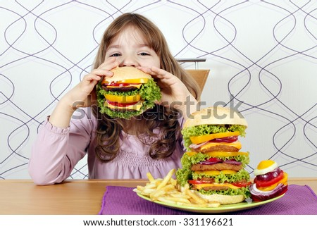 hungry little girl eating a big hamburger  - stock photo