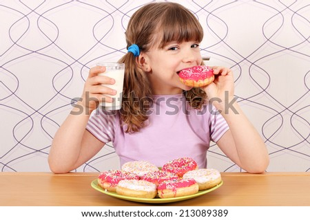 hungry little girl eating donuts and drink milk - stock photo