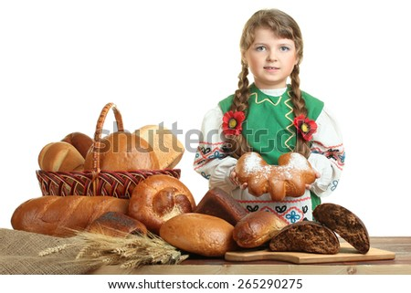 Hungry little girl with a bun at the table - stock photo
