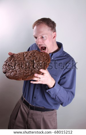 Hungry man eating a giant cookie - stock photo
