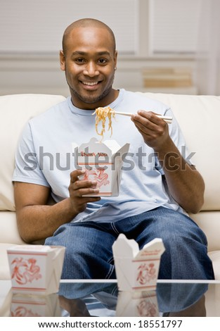 Hungry man eating chinese take-out food with chopsticks in livingroom