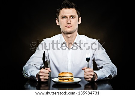 Hungry man in the white shirt is going to eat a burger