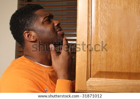 Hungry man looking for food in kitchen cabinet