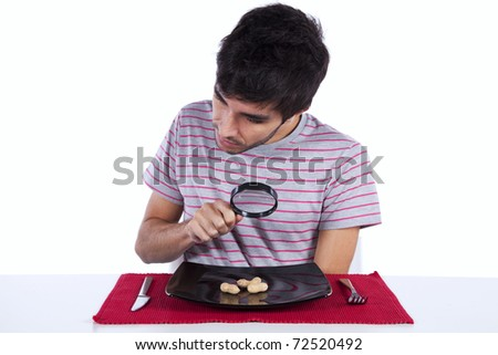 Hungry man looking to a peanut with a magnifying glass