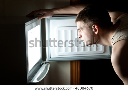 Hungry man opening fridge. - stock photo