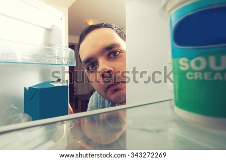 hungry man with funny face opens the fridge - stock photo