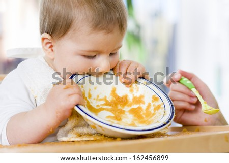 Hungry messy baby boy bitting the plate after eating vegetable puree. - stock photo