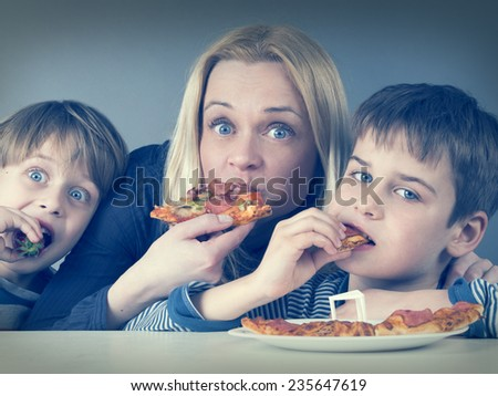 Hungry mother and kids, eating pizza together - stock photo