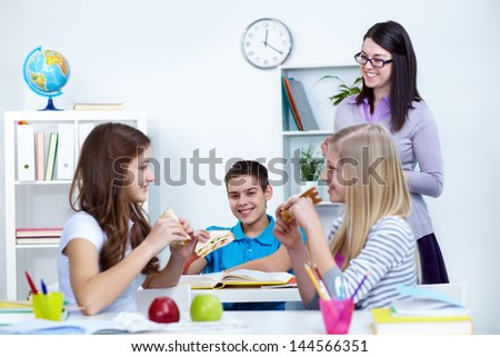 Hungry students eating sandwiches during break in college with their teacher near by - stock photo