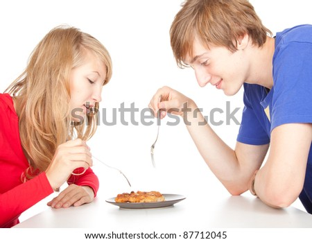 hungry teenage couple eating cakes, white background