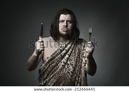 Hungry wild man wearing leopard skin hold fork and knife. - stock photo