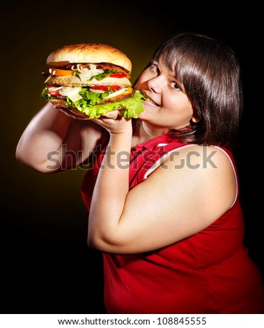 Hungry woman eating big hamburger.