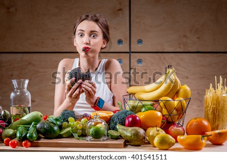 Hungry woman eating black burger at the table full of fruits and vegetables on the wooden background. Choosing between healthy and unhealthy food - stock photo