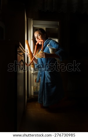 hungry woman eating food near refrigerator - stock photo