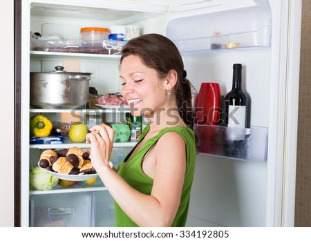 Hungry woman near opening fridge eating cakes - stock photo